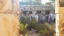 Männer beten in den Ruinen