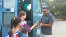 Schülerinnen bekommen Süßigkeiten beim Einstieg in den Schulbus. Foto: Regionalverwaltung Südhevron